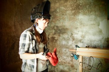 Woman preparing to weld wire frame otter.